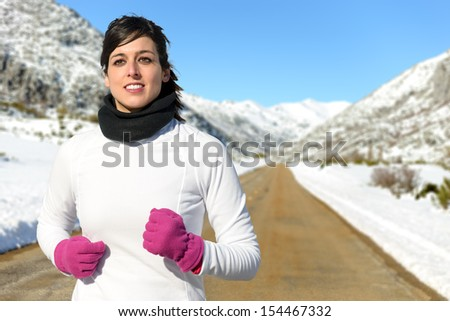 Woman running in cold winter in snowy mountain country side road. Female athlete in warm sportswear and gloves training and exercising. - stock photo