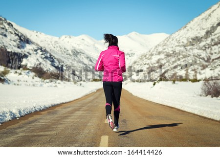 Woman running in cross country road on winter. Rear view of female runner training for marathon in snowy mountains landscape. - stock photo