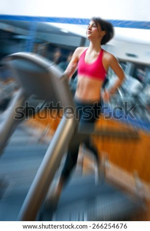 woman running in gym on automatic track machine, zoomed for dramatic presentation effect - stock photo