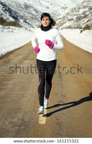 Woman running  in winter. Girl exercising on a mountain road on a snowy natural scenery. - stock photo