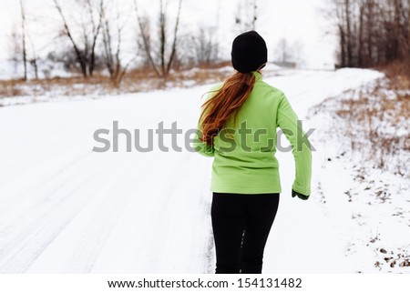 Woman running in winter snow. Fitness and health concept.