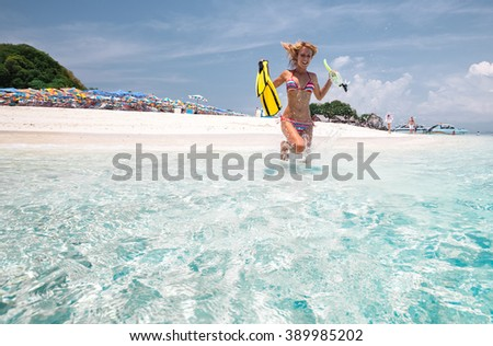 Woman running into the tropical sea with fins and snorkeling gear