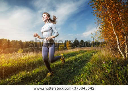 Woman running off road in an autumn forest - stock photo