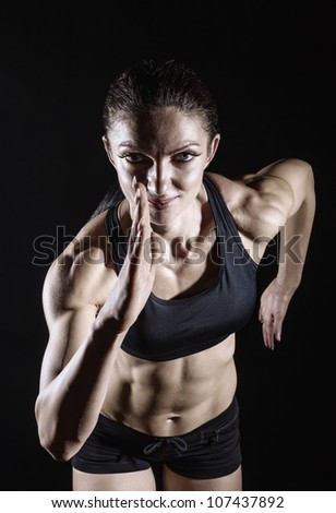 Woman running on a dark background. Front view - stock photo
