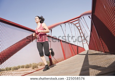 woman running on a footbridge to sunny day - stock photo