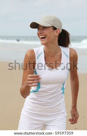 Woman running on a sandy beach - stock photo
