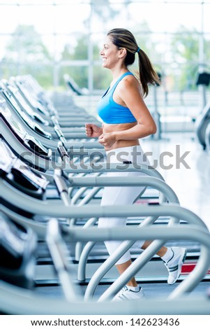Woman running on a treadmill at the gym - stock photo