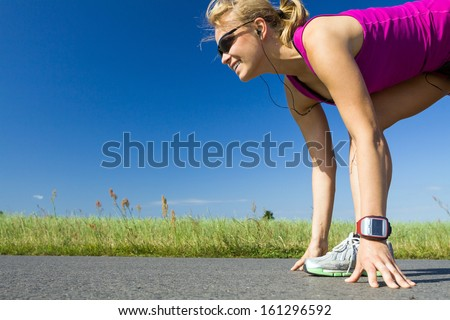 Woman running on country road. Young female runner ready to run on asphalt in summer sunny nature outdoors, sport and fitness. - stock photo