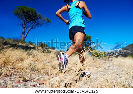 woman running on nature trail sunny day blue sky and jumping athlete - stock photo