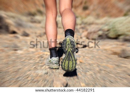 Woman running on trail. Zoom motion blurred closeup of woman trail running in desert on the volcano Teide, Tenerife. - stock photo