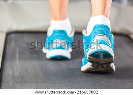 Woman running on treadmill in gym. - stock photo