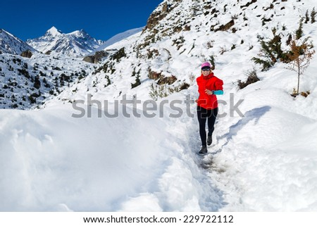 Woman running on white snow in Himalaya Mountains in Nepal. Adventure cross country runner on snow trail in beautiful mountain landscape. Motivation and inspiration fitness activity. - stock photo