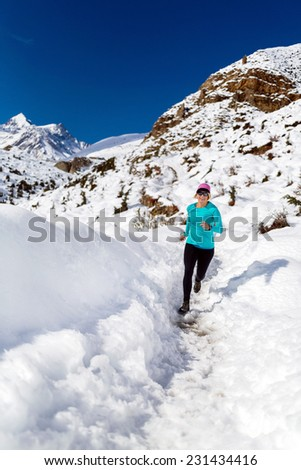 Woman running on white snow in Himalaya Mountains in Nepal. Adventure cross country runner on snow trail in beautiful mountain landscape. - stock photo
