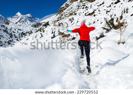 Woman running on white snow in Himalaya Mountains in Nepal. Motivation and inspiration fitness activity. Adventure cross country runner on snow trail in beautiful mountain landscape. - stock photo