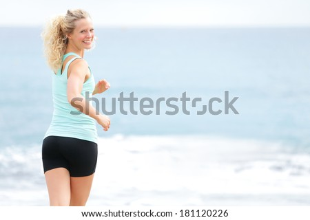 Woman running outside on beach looking back jogging. Female fitness runner girl jogger training outdoors by the ocean sea. Beautiful young blonde woman in her 20s training. - stock photo