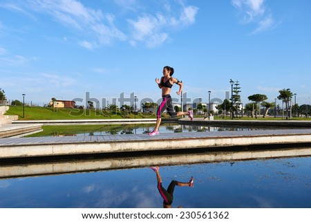 woman running over bridge with fitness marathon training stride - stock photo