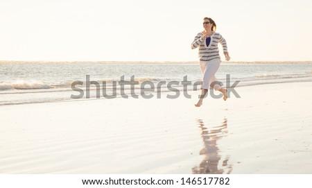 Woman Running Playfully on the Beach - stock photo