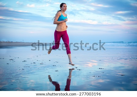 Woman running through water on the beach at sunset - stock photo