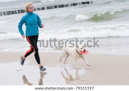 Woman running with dog on the beach