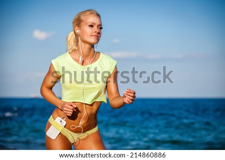 Woman running with earphones on sea background. Caucasian beautiful fitness girl working out on summer - stock photo