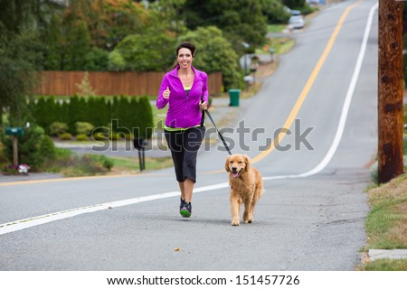Woman running with her golden retriever dog - stock photo