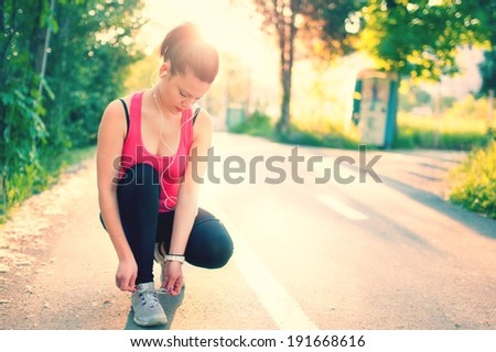 woman running workout on spring sunny sunset. Fitness girl getting ready for jogging in city park - stock photo