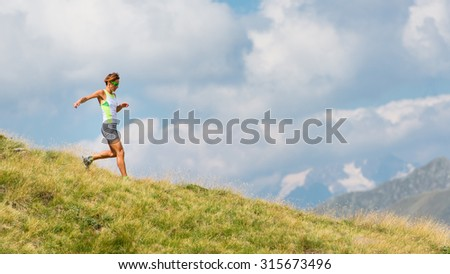Woman runs in the mountains in the meadow alone
