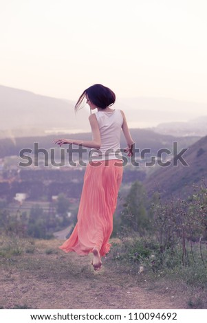 Woman runs up the hill at sunset - stock photo