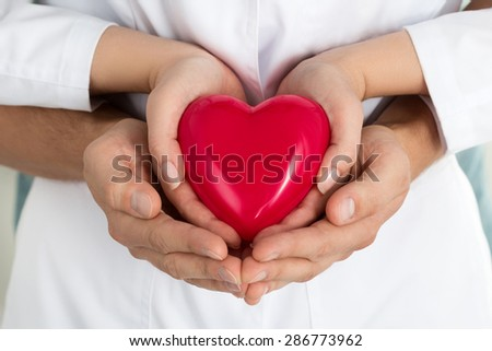 Woman's and man's hands holding red heart together. Love, assistance and healthcare concept - stock photo