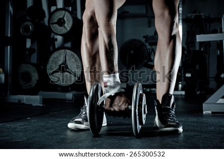 Woman's arm and legs with barbells in the gym - stock photo