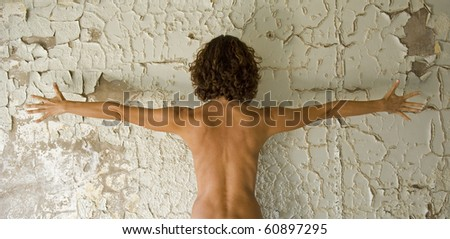 Woman's back on grunge wall. - stock photo