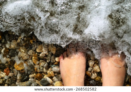 Woman's barefoot legs in a warm sea. Enjoying summer time vacation. - stock photo