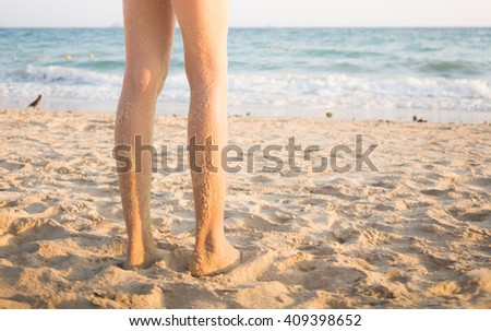 woman's beautiful legs on sand beach