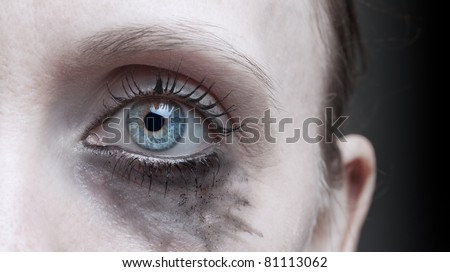 Woman's eye with running makeup - stock photo