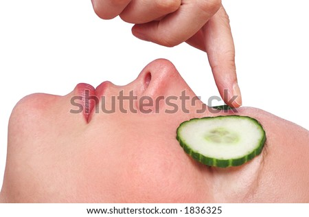 Woman's face with cucumber slices and finger - stock photo