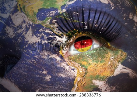 woman's face with planet Earth texture and german flag inside the eye. Elements of this image furnished by NASA. - stock photo