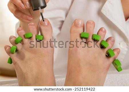 Woman's feet in pedicure toe separators at the nail salon. Beautician applying nail polish  - stock photo