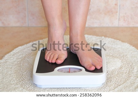 Woman's feet on bathroom scale. Diet concept - stock photo