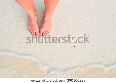 Woman's feet on the white sand beach in shallow water - stock photo