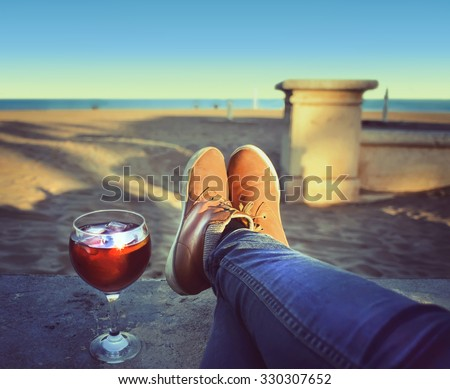 Woman's  Feet relaxing on the beach enjoying sun on sunny spring day,wineglass  of sangria . Valencia, Spain - stock photo