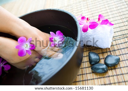 Woman's feet soaking in bowl of floral scented water - stock photo