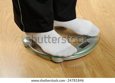 Woman`s feet standing on a weight scale on wooden floor