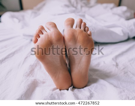 Woman's feet under the blanket
