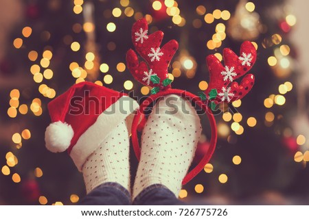 Woman's feet wearing warm winter socks, antlers and Santa's hat, placed on the table with Christmas tree and Christmas lights in the background. Selective focus on the antlers