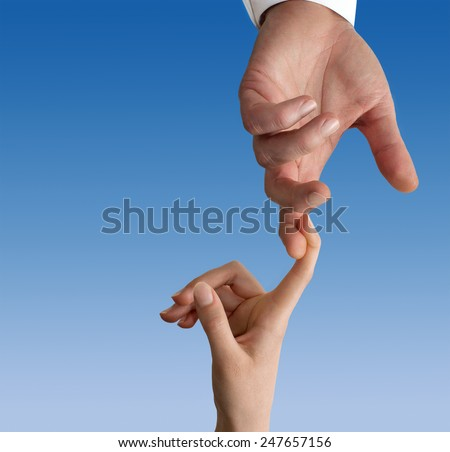 Woman's finger hanging on a man's one in a blue sky background - stock photo