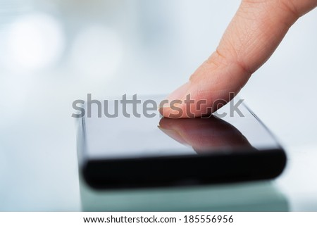 Woman's finger touching smartphone on table in office