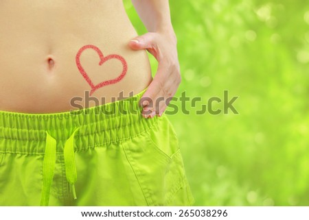 Woman's fit belly with heart and athletic pants,on green bokeh background - stock photo