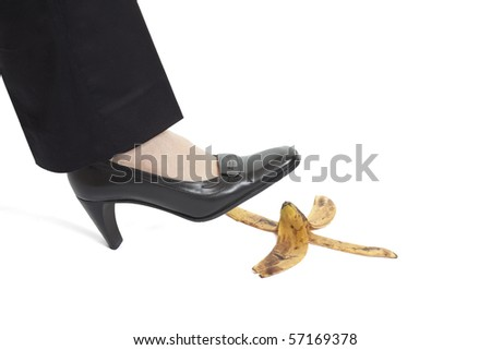 Woman's foot about to slip on banana peel - stock photo