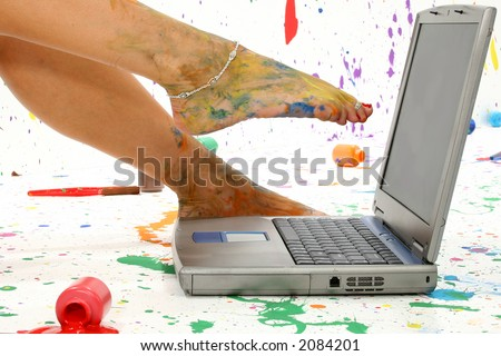 Woman's foot on laptop. Surounded by splattered paint.