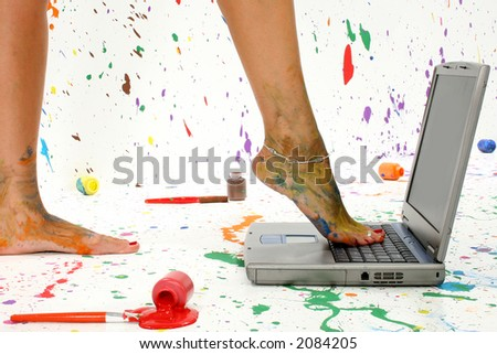 Woman's foot on laptop. Surounded by splattered paint. - stock photo